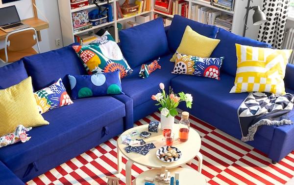 Un divano angolare blu con cuscini colorati, due tavolini tondi e un tappeto a righe - IKEA