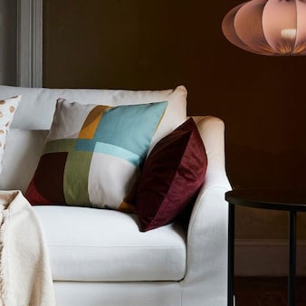 Un divano FÄRLÖV bianco con diversi cuscini e un plaid, vicino a un tavolino nero e a una lampada a sospensione con paralume REGNSKUR - IKEA