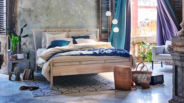 Un dormitor albastru-gri cu un pat dublu din lemn și perdele turcoaz și mov care flutură în vânt.