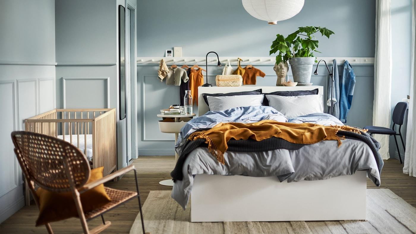 Un dormitor în albastru deschis, cu un pat alb, un corp de iluminat alb, un panou alb cu cârlige, un balansoar din ratan și un pătuț SNIGLAR.