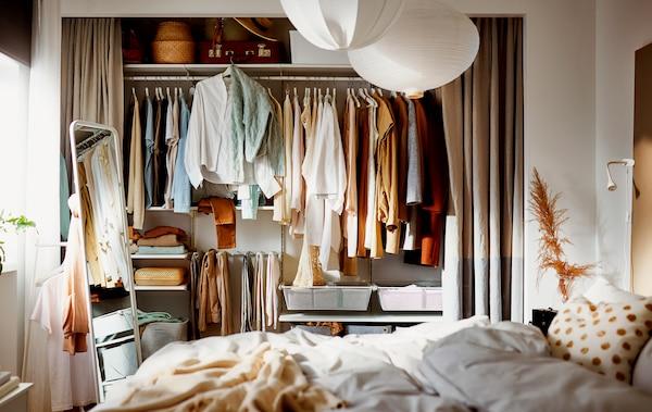 Un dormitor în care un alcov având lățimea întregului perete are perdelele trase lăsând să se vadă un dulap de haine plin construit pe o combinație de corpuri de depozitare BOAXEL.