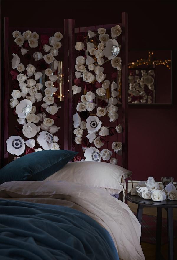 Un dormitor roșu închis cu un pat cu lenjerie albă și albastră și un paravan cu motive florale.