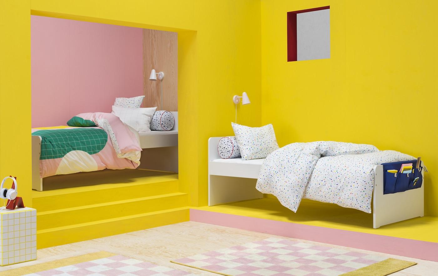 Un dormitor roz aprins și galben cu două paturi individuale cu cuverturi colorate și modele grafice.