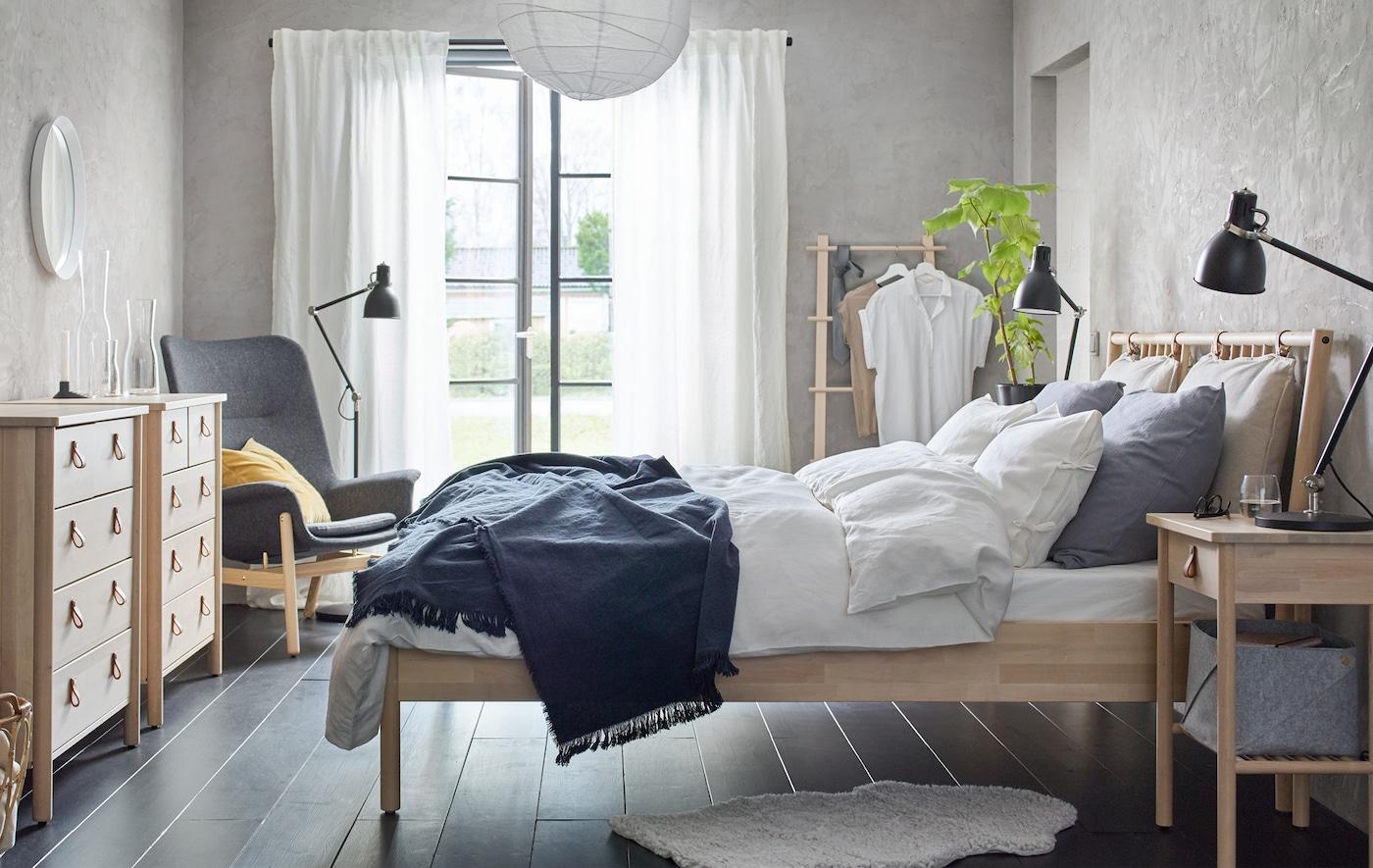 Un dormitori amb decoració en tons neutres amb una estructura de llit de fusta, una còmoda amb calaixos i una tauleta de nit.