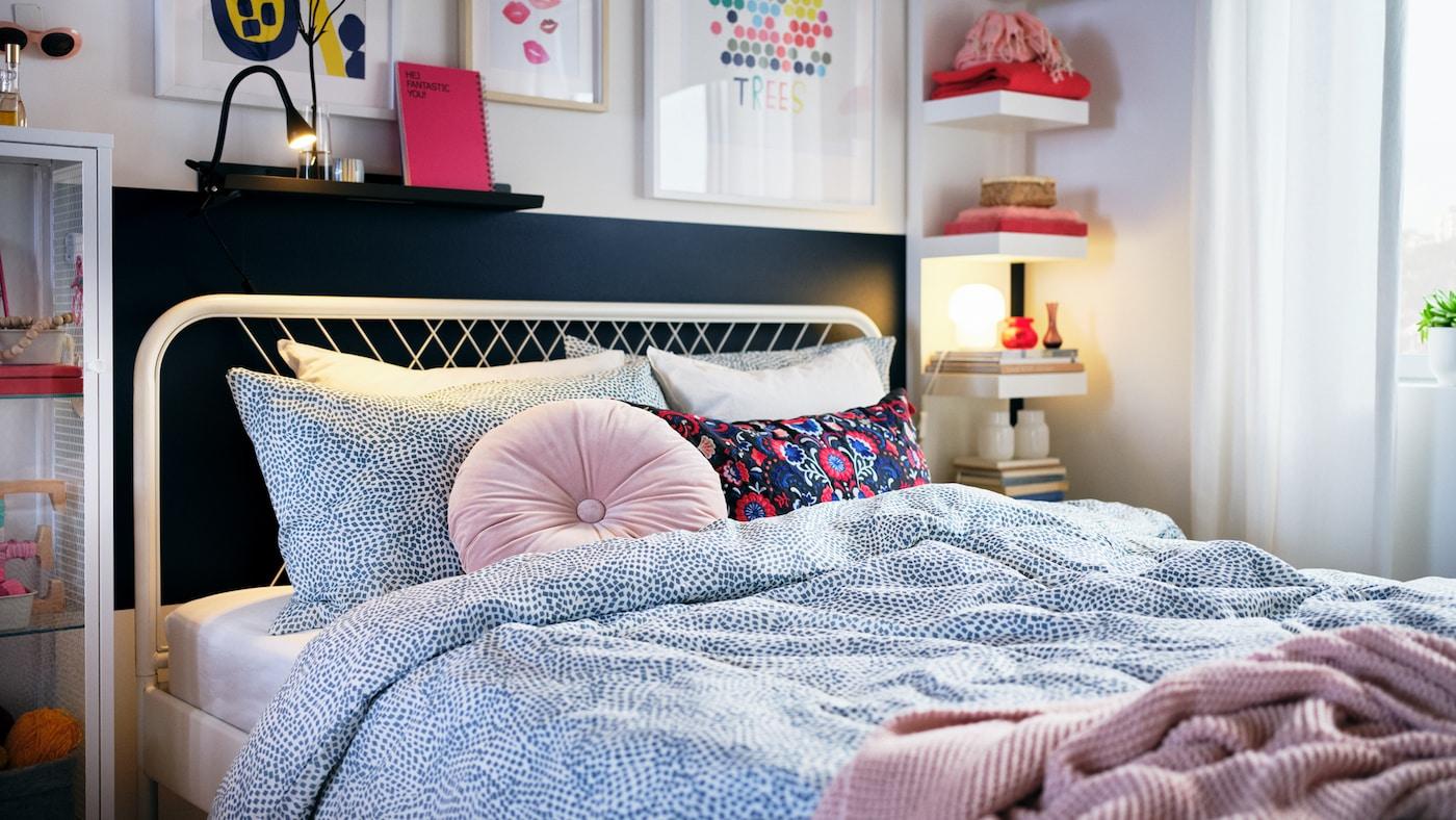Un dormitori clar amb decoracions de colors i un llit blanc NESTTUN fet amb roba de llit en color blau i blanc TRÄDKRASSULA.
