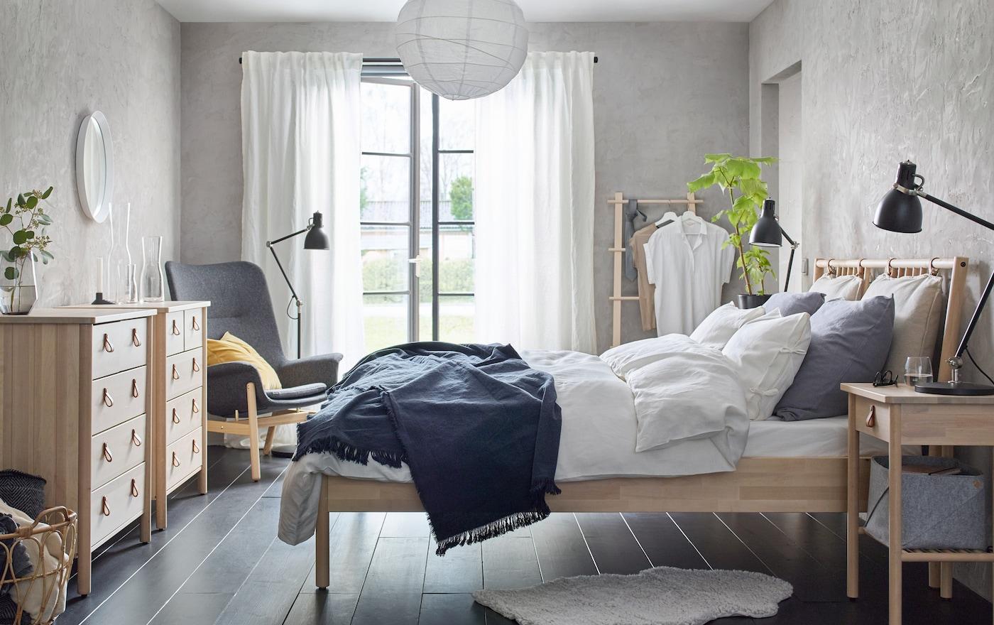 Un dormitorio beige y gris con nuestra serie BJÖRKSNÄS de cama, mesita de noche y cómoda de 5 cajones de madera maciza de abedul.
