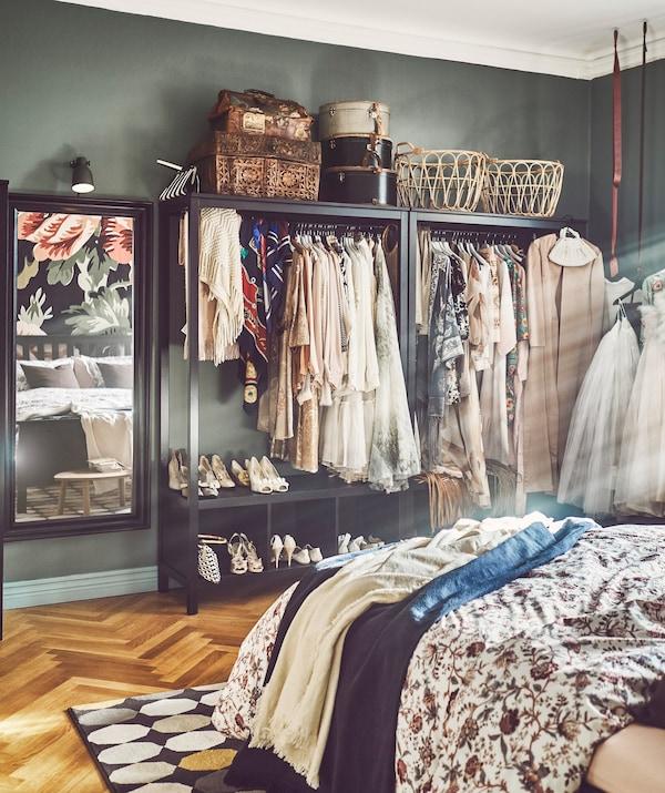Un dormitorio con armarios abiertos de IKEA HEMNES con ropa y zapatos expuestos.