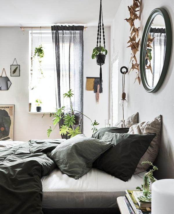 Un dormitorio con paredes blancas, ropa de cama verde y plantas en macetas.