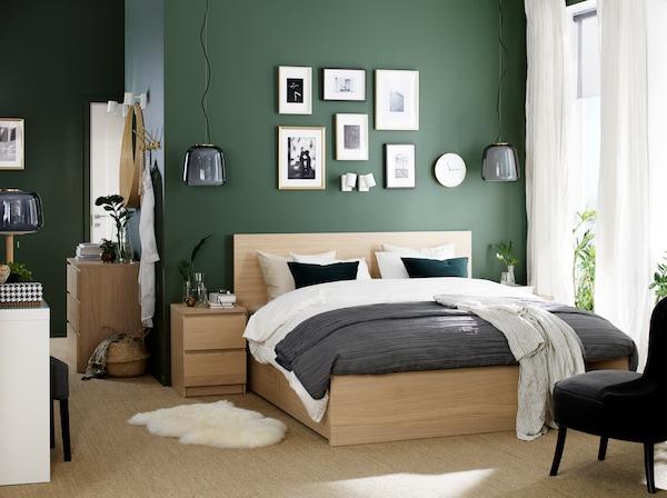 Un dormitorio con una estructura de cama y mesita de noche chapada en roble teñido de blanco, un tocador blanco y un sillón gris.