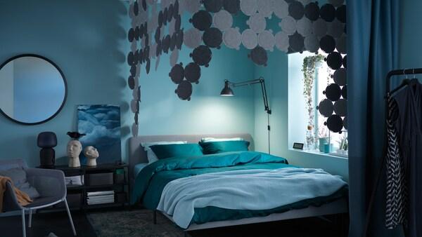 Un dormitorio cunha cama SLATTUM xunto a unha fiestra. Sobre a cama, un dosel feito de paneis de absorción de son ODDLAUG.