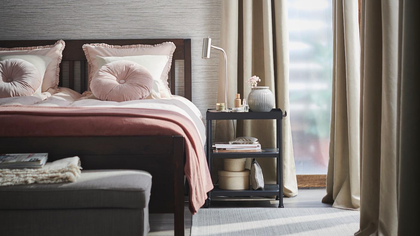Un dormitorio donde está la cómoda o velador IDANÄS negro y sobre el hay decoración y lámpara de escritorio. Al lado del mueble hay una cama con cobertores rosados y rosa.