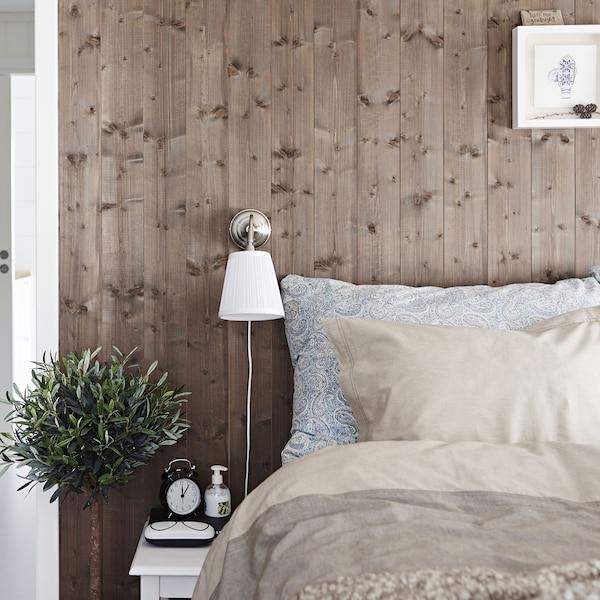 Un dormitorio en marrón con una cama, ropa de cama y una lámpara de pie junto a la cama.