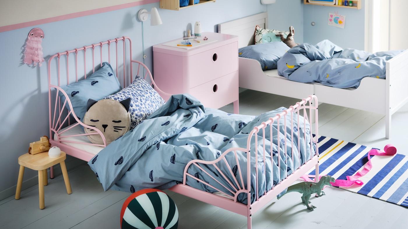 Un dormitorio infantil con una cama extensible MINNEN en rosa claro y una cama blanca hecha con ropa de cama VÄNKRETS y BARNDRÖM en azul.