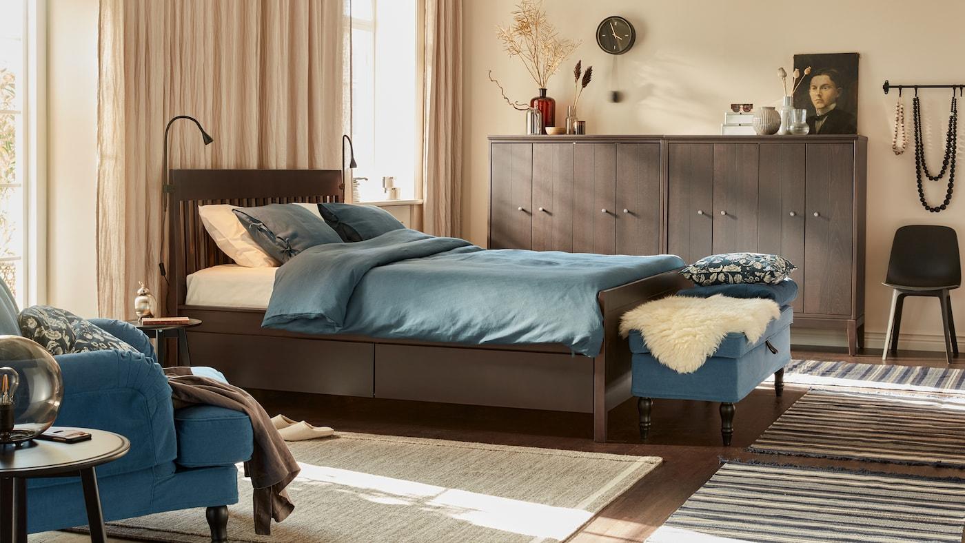 Un dormitorio tranquilo con paredes beige, cortinas de lino, una cama de madera, textiles en azul oscuro, un banco y armarios de madera junto a las paredes.