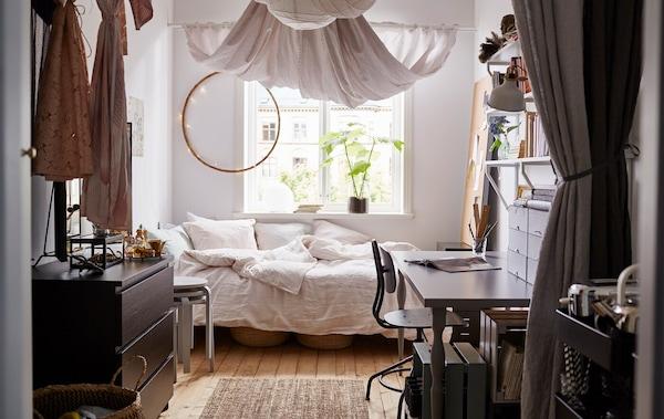 Un dormitorio universitario desde la entrada. Del techo cuelgan tejidos de colores claros.