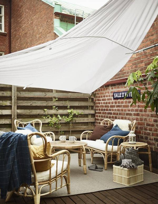Un dosel IKEA DYNING protege un sofá de exterior, dos sillones y algunas mesas del sol en la terraza.