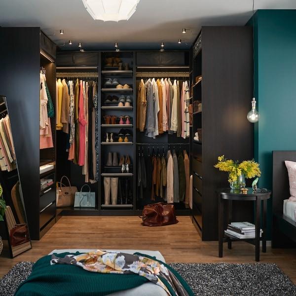 Un dressing PAX din lemn de culoare închisă, amplasat într-o cameră văruită în albastru-turcoaz. O cuvertură decorativă turcoaz este așezată pe un pouf.