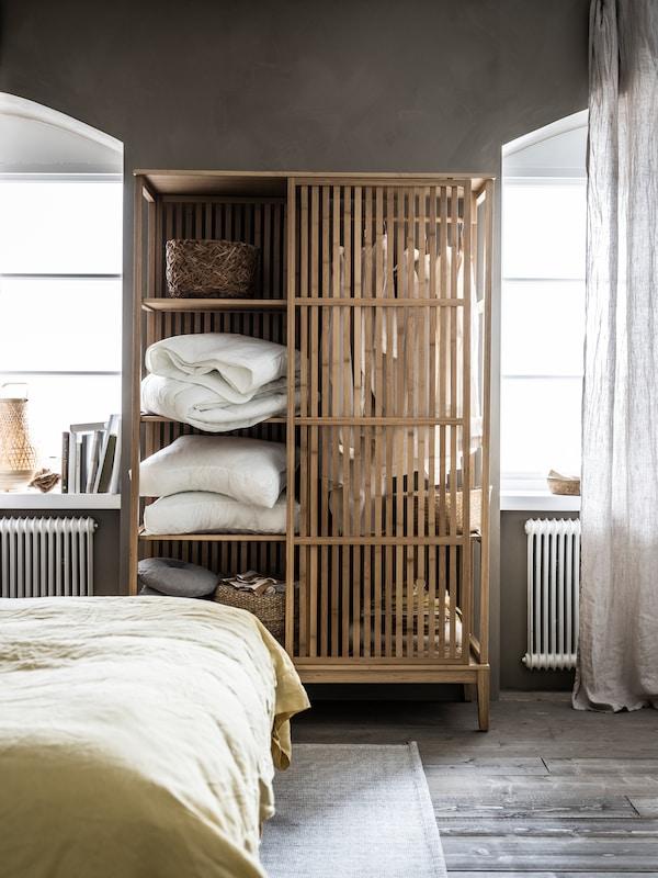 Un dulap deschis NORDKISA plin cu pilote, perne, decorațiuni și haine este amplasat între cele două ferestre ale dormitorului.