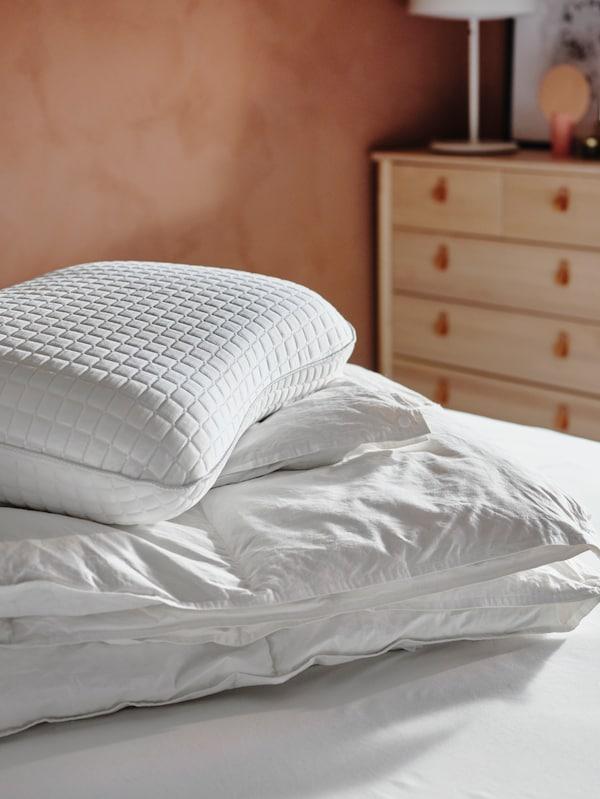 Un edredó FJÄLLARNIKA i un coixí ergonòmic KLUBBSPORRE apilats sobre un llit en un dormitori il·luminat pel sol.