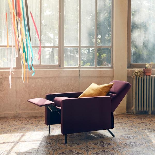 Un élégant fauteuil inclinable GISTAD d'une couleur rouge foncé raffinée en position allongée dans le milieu d'une pièce.