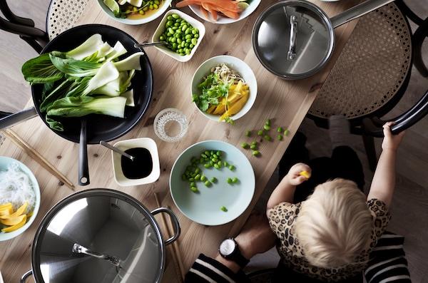 Un enfant assis sur les genoux d'un adulte à une table en bois mange avec ses doigts des fruits en tranches et des légumes disposés dans des bols et poêlons.