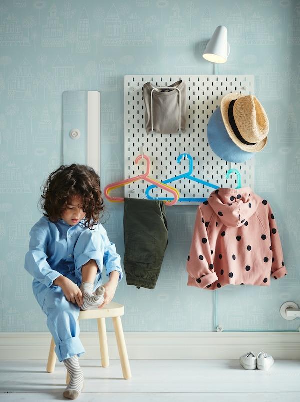 Un enfant assis sur un tabouret qui enfile des chaussettes devant un panneau perforé SKÅDIS où sont suspendus divers articles vestimentaires.
