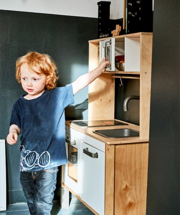 Un enfant jouant avec une mini cuisine.