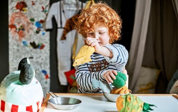 Un enfant joue avec des peluches à table.