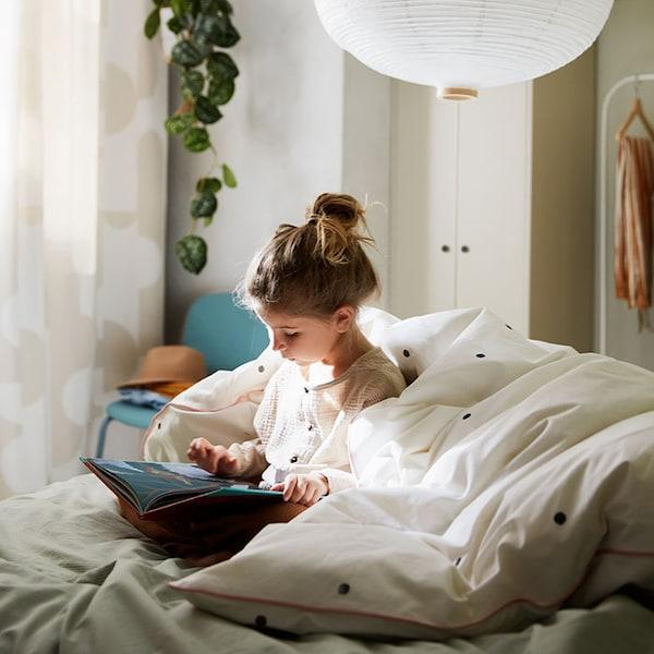 Un enfant qui lit un livre, blottie dans un lit douillet avec une couette en rayures vertes et blanches BERGPALM.