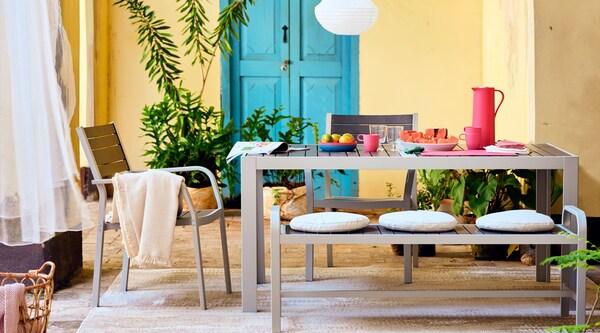 Un ensemble de salle à manger SJÄLLAND noir et argent, dans un espace repas extérieur, avec des plats et des verres.