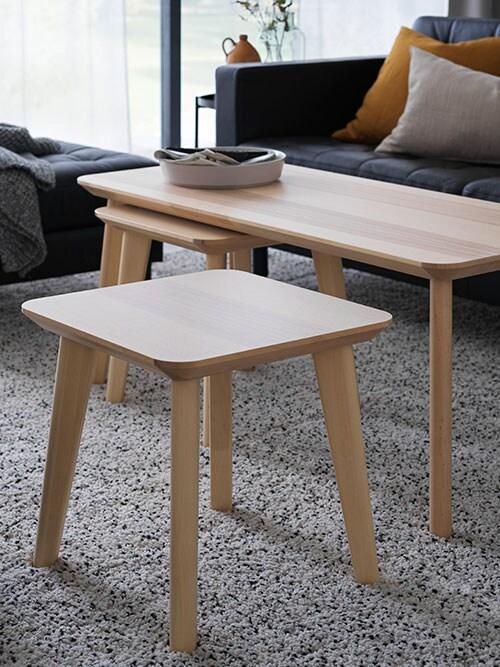 Un ensemble de trois tables gigognes en bouleau plaqué posées sur un tapis gris, avec un canapé en arrière-plan.