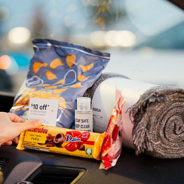 Un ensemble pour ciné-parc comprenant une couverture grise enroulée, des croustilles, du chocolat, des bonbons, du désinfectant pour les mains et un bon pour IKEA.