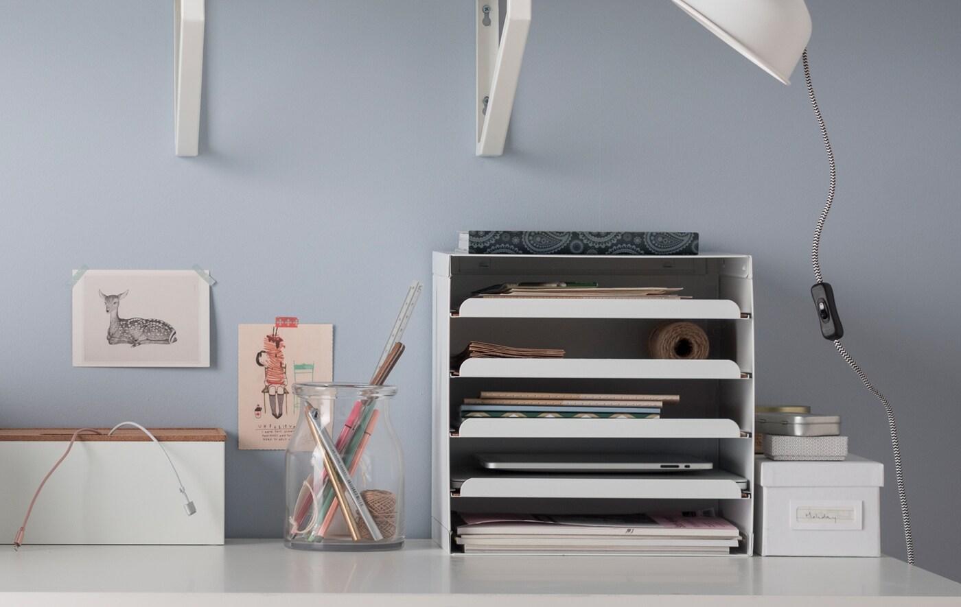 Un escritorio blanco con soluciones de organización prácticas: una bandeja para documentos y tabletas, cajas, un organizador de cables y un tarro de vidrio para bolígrafos.