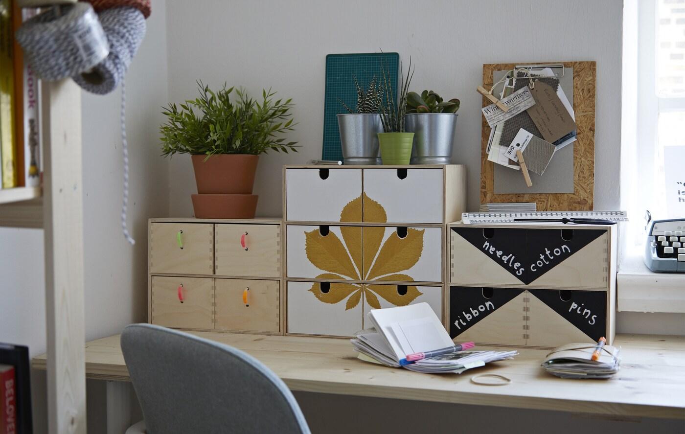 Un escritorio con caixóns para organizar, personalizados con algún motivo, pintura e tiradores coloridos.