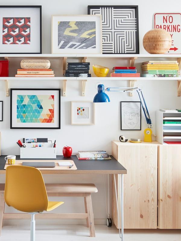 Un escritorio con ruedas se encuentra junto a una pared, rodeado de gabinetes IVAR de madera clara, estantes de pared y obras de arte enmarcadas.