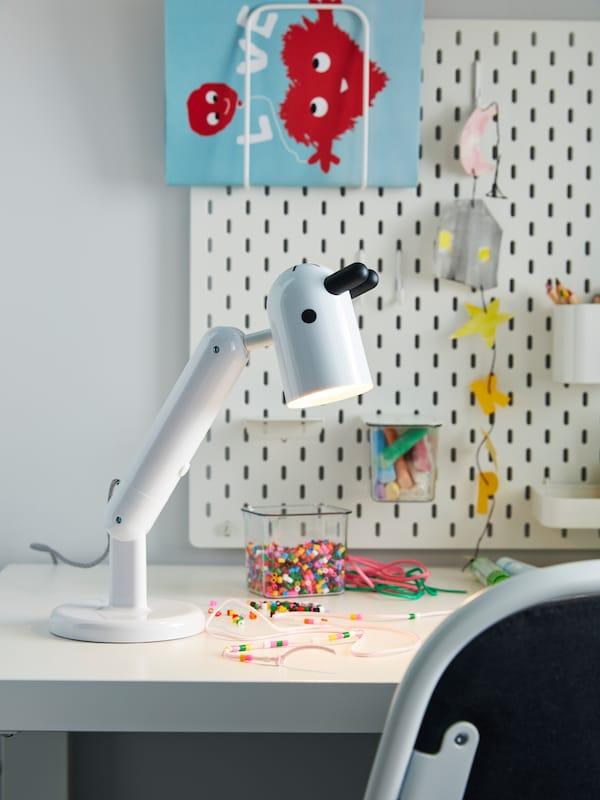 Un escritorio con una lámpara KRUX de IKEA, que tiene forma de cabeza de animal con orejas y nariz, en blanco y negro, de IKEA.