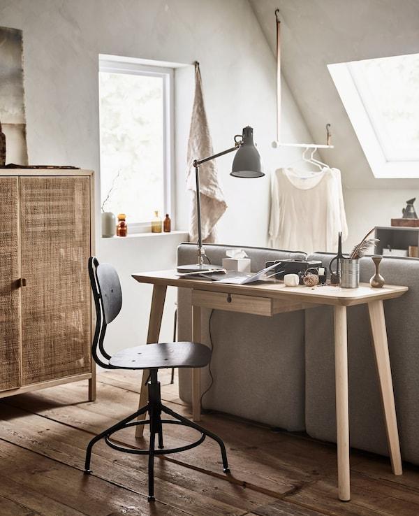 Un escritorio pequeño y silla justo delante de un sofá cama.