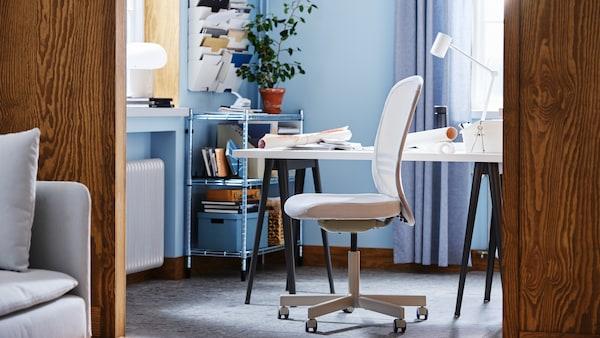 Un espace de travail avec des murs bleus, un bureau, une chaise de bureau beige FLINTAN, une étagère galvanisée avec des boîtes et une plante.
