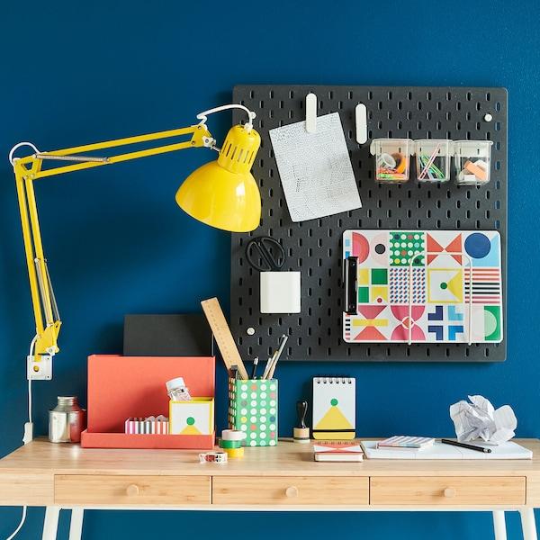 Un espace de travail coloré avec un bureau en bambou, une lampe jaune et un panneau perforé peint en noir, sur lequel sont accrochés des articles de papeterie.