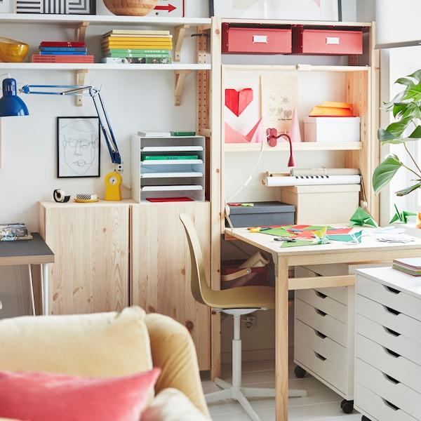 Un espace de travail comprend un rangement IVAR à une section, avec une table pliante, un élément IVAR, des caissons à tiroirs ALEX et une chaise pivotante.