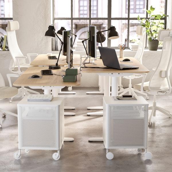 Un espace de travail ouvert avec quatrebureaux, quatrechaises pivotantes, quatrelampes de bureau et deuxcaissons à tiroirs.