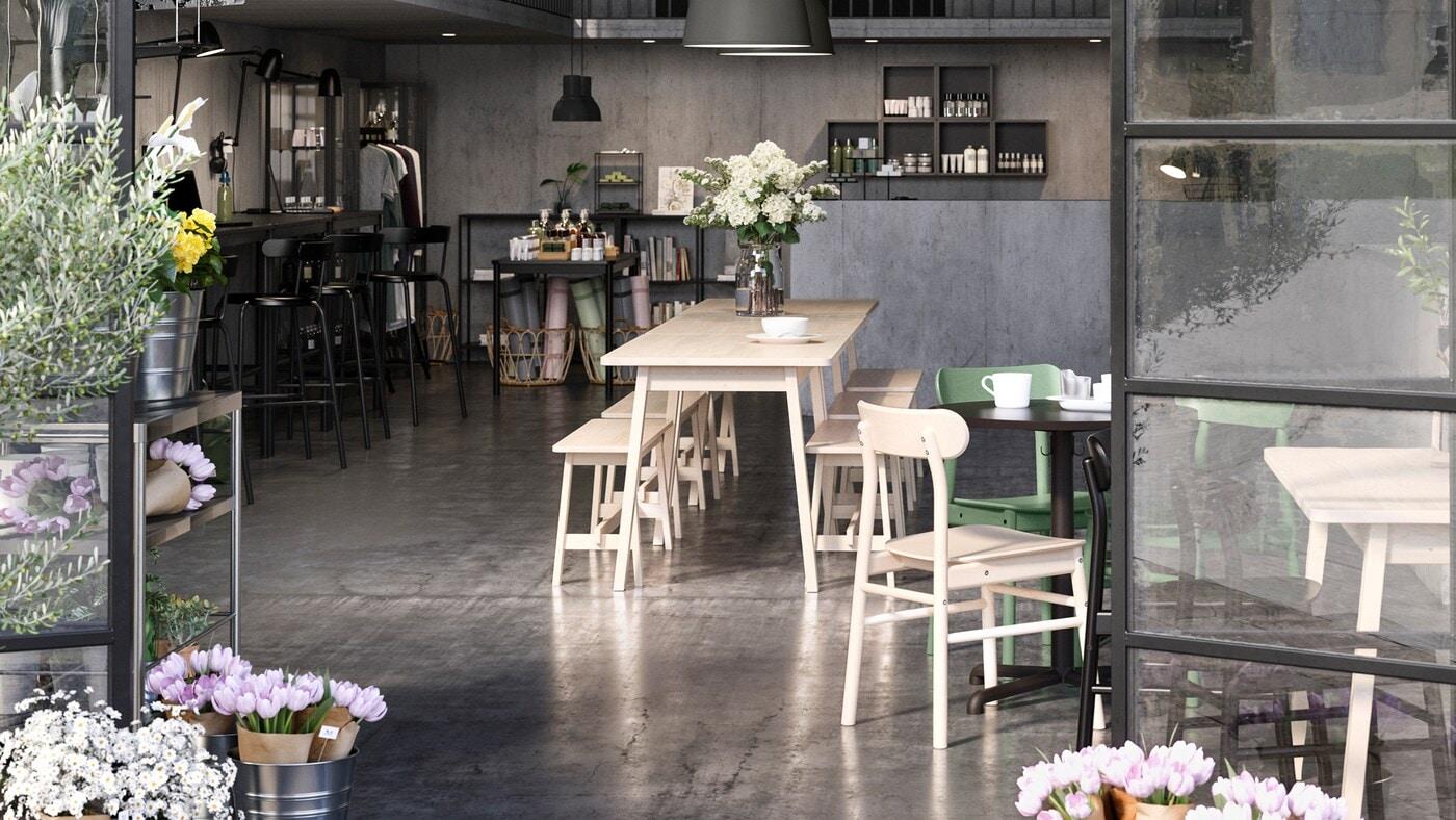 Un espace de travail partagé ouvert servant aussi de café et de boutique, encadré par des portes en verre ouvertes. Des fleurs sont sur la table et près des portes.