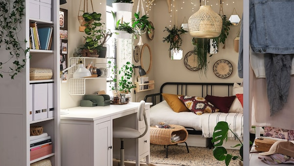 Un espace de vie polyvalent boho chic avec des guirlandes lumineuses, plusieurs plantes suspendues, une décoration éclectique et des accents boho en osier.