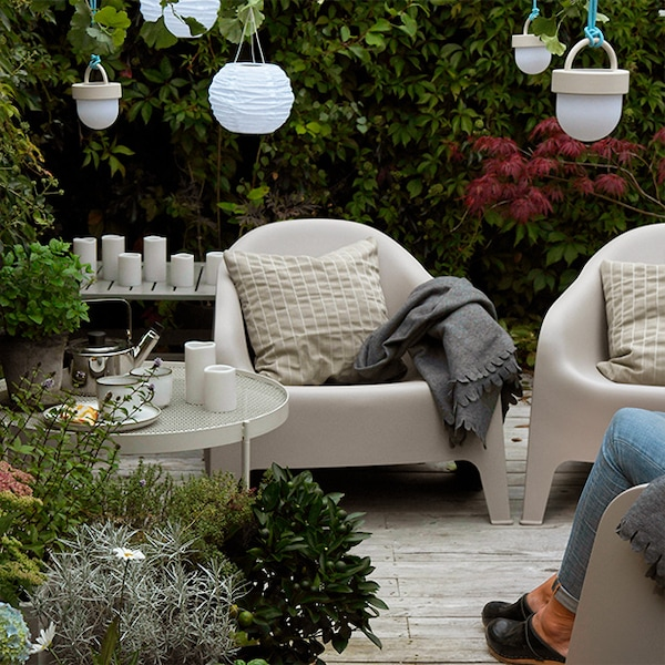 Un espace extérieur avec des chaises longues de patio, beaucoup de verdure et de plantes et quelques décorations lumineuses.