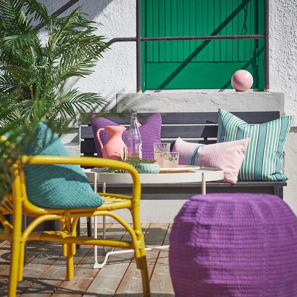 Un espace extérieur avec un pouf violet et des coussins colorés résistants aux intempéries.