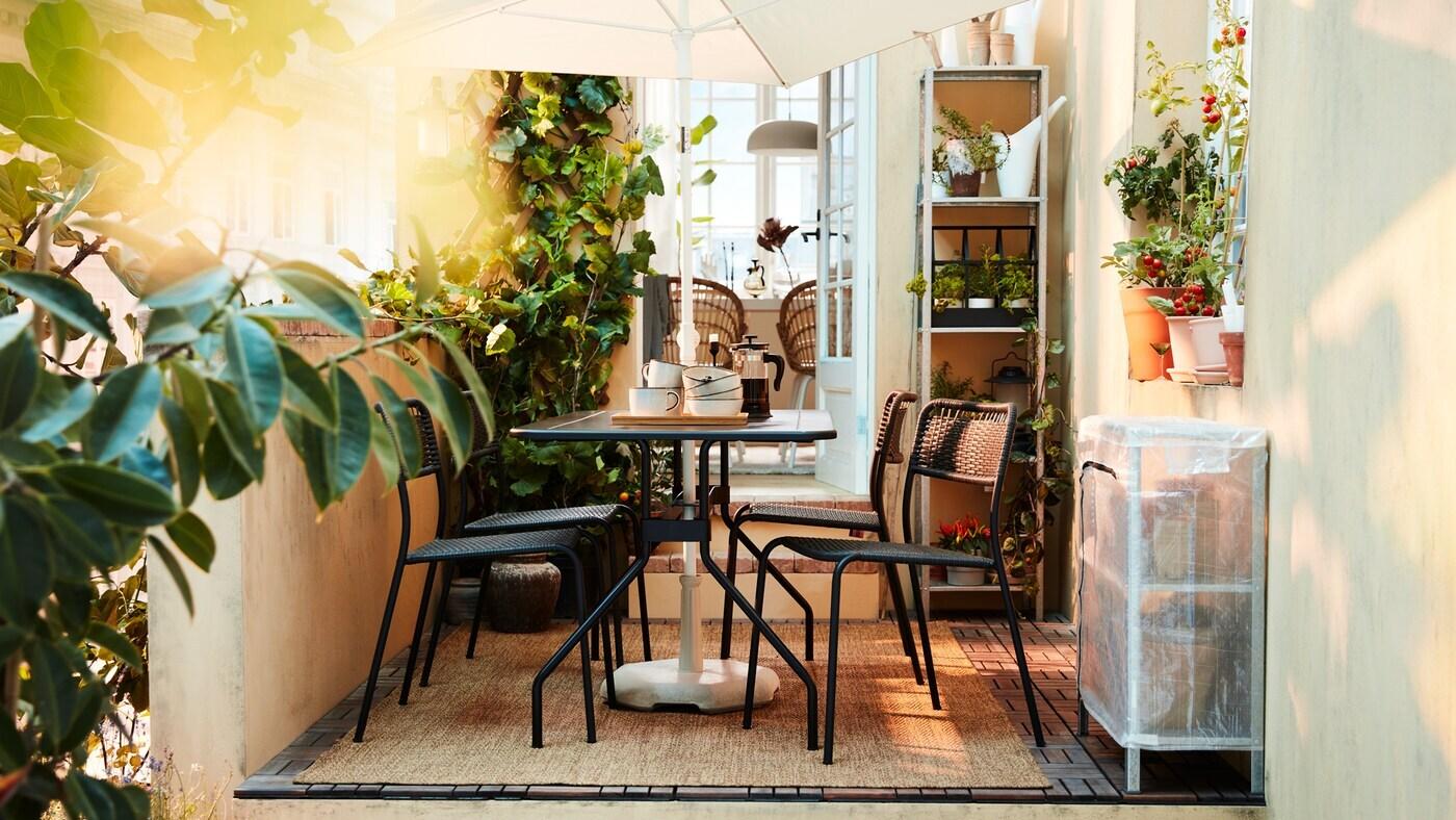 Un espace extérieur luxuriant avec des meubles de salle à manger noirs, un parasol blanc, beaucoup de plantes et un tapis tissé.