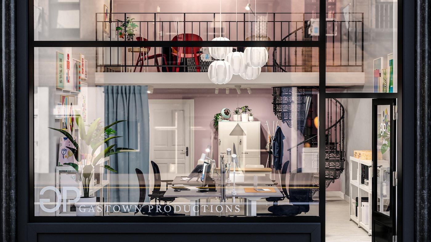 Un espacio de oficina con un loft, escritorios para trabajar de pie/sentado, sillas de oficina negras, una escalera, cortinas azules y paredes rosas.