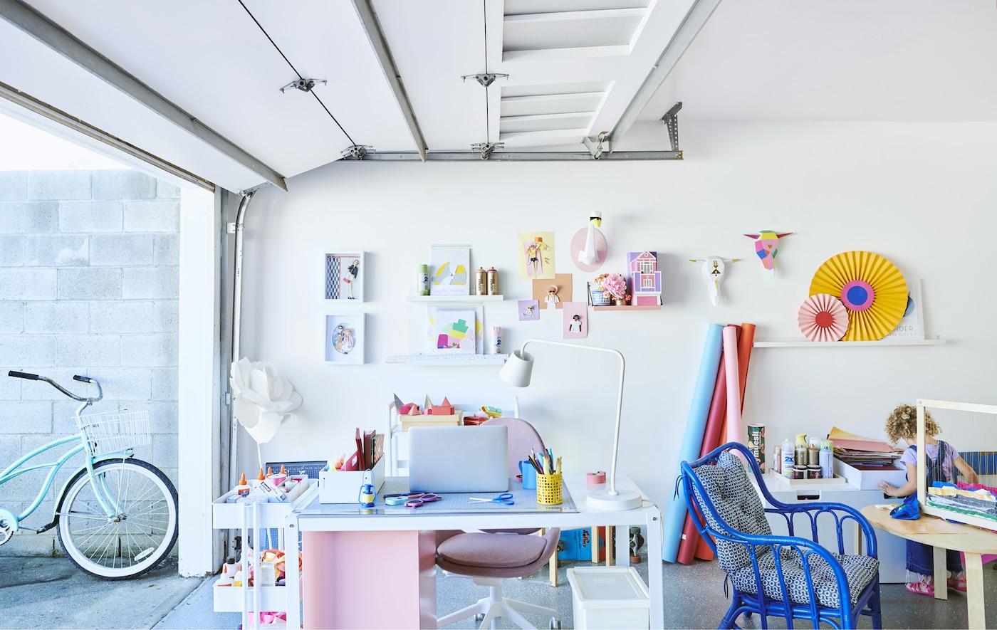 Un espacio de trabajo colorido con un escritorio, un carrito, sillas y expositores de pared, en un garaje con la puerta corredera abierta.