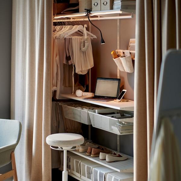 Un espacio de trabajo dentro de un sistema de almacenaje BOAXEL blanco detrás de unas cortinas, con iluminación y un soporte para trabajar de pie/sentado.