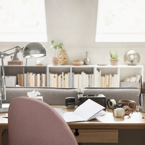Un espacio de trabajo doméstico con una lámpara de trabajo, una silla giratoria y un escritorio LISABO chapado en fresno detrás de un sofá.